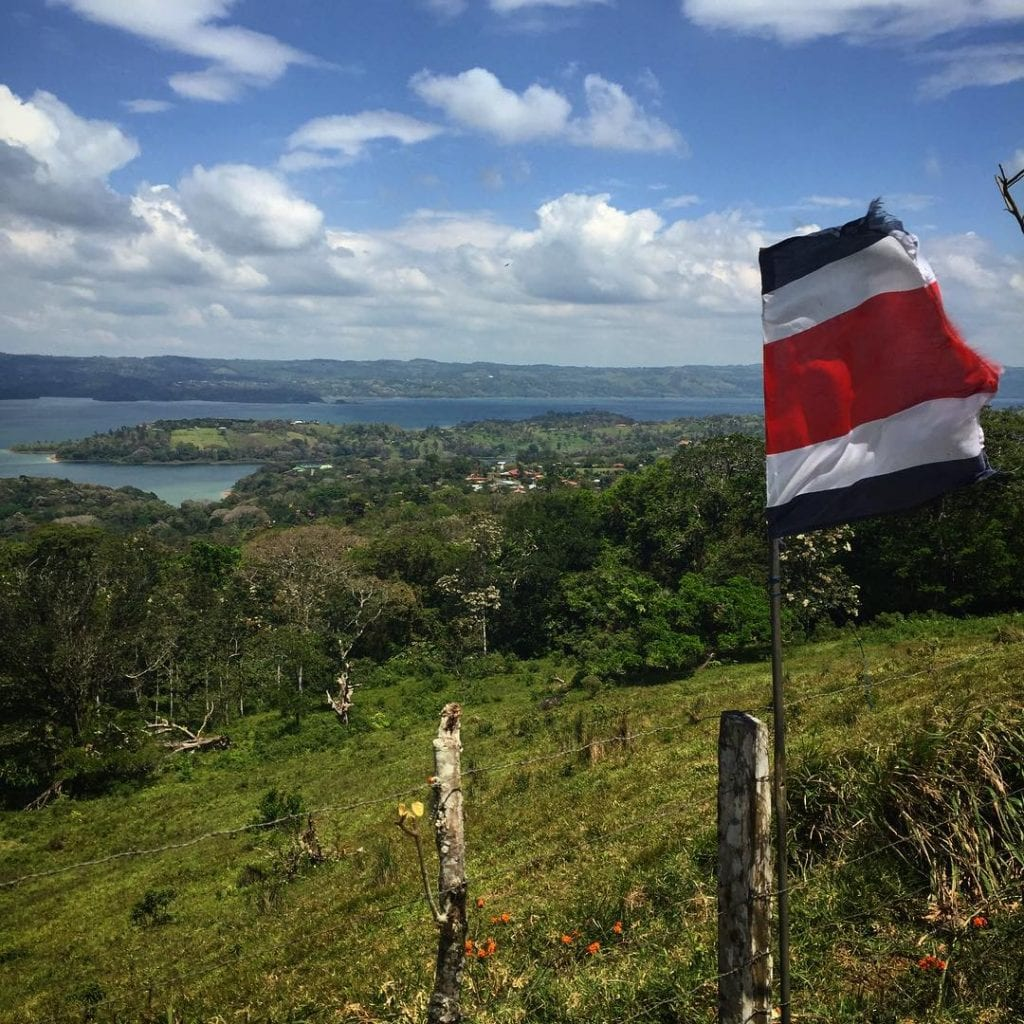 Costa Rican flag waving over Lake Arenal, photo credit @hanka_slavickova